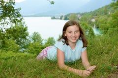 Muchacha bastante pre adolescente que miente en hierba Fotografía de archivo