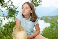 Muchacha bastante pre adolescente que se sienta en hierba Imagen de archivo libre de regalías