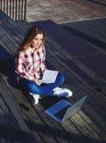 Muchacha bastante rubia con el pelo largo que se sienta en el estadio con un libro y un ordenador Imagen de archivo libre de regalías