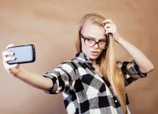 Muchacha bastante rubia del inconformista de los jóvenes que hace el selfie en el fondo marrón caliente, concepto de la gente de  Fotos de archivo