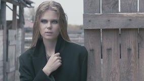 Muchacha bastante rubia en un negro cerca de la cerca en un día nublado metrajes