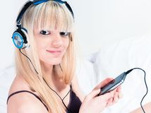 Muchacha bastante rubia que escucha la música en su smartphone Foto de archivo
