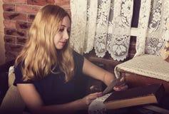 Muchacha bastante rubia que lee un libro y que mira la foto Imagenes de archivo