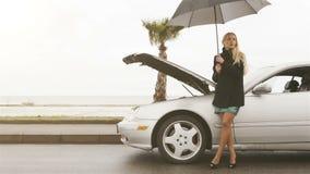 Muchacha bastante rubia que mira ayuda que espera cerca de su coche quebrado almacen de video
