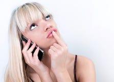 Muchacha bastante rubia que reflexiona mientras que llama por teléfono Imagenes de archivo