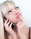 Muchacha bastante rubia que reflexiona mientras que llama por teléfono Foto de archivo libre de regalías