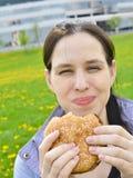 Muchacha beautuful feliz que come la hamburguesa Fotografía de archivo