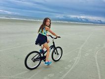 Muchacha biking en la playa imagen de archivo