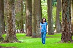 Muchacha biracial adolescente joven que camina debajo de árboles altos Fotografía de archivo