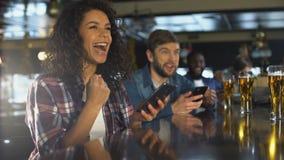 Muchacha Biracial en barra que celebra la apuesta acertada en deportes, app en línea del corredor almacen de video
