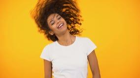 Muchacha biracial sincera que agita el pelo rizado y el baile, sonriendo en felicidad de la cámara almacen de metraje de vídeo
