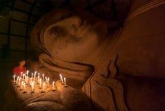 Muchacha birmana no identificada que ruega con la luz de la vela en un templo de Buddihist el 5 de enero de 2011 en Bagan Imagen de archivo