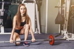 Muchacha blanca atractiva de la aptitud en un gimnasio que hace deadlifts imagen de archivo