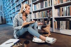 Muchacha blanca cerca del estante en biblioteca El estudiante está escuchando la música, usando el ordenador portátil y el libro  imagenes de archivo