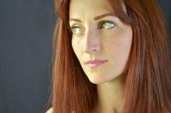 Muchacha blanca con el pelo rojo y los ojos verdes con extensiones de la pestaña en el fondo gris que mira seriamente para arriba foto de archivo libre de regalías