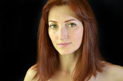 Muchacha blanca con el pelo rojo y los ojos verdes con extensiones de la pestaña en el fondo negro que mira adelante imagen de archivo libre de regalías