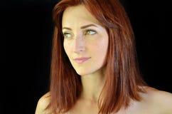 Muchacha blanca con el pelo rojo y los ojos verdes con extensiones de la pestaña en el fondo negro que parece correcto fotografía de archivo