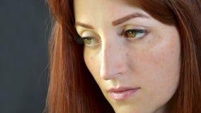 Muchacha blanca con el pelo rojo y los ojos verdes con extensiones de la pestaña en el fondo oscuro que mira seriamente abajo fotografía de archivo libre de regalías