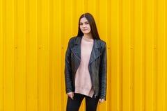 Muchacha blanca en una presentación negra de la chaqueta al aire libre cerca con la pared amarilla Imagenes de archivo