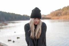 Muchacha blanda en un suéter y un sombrero calientes que presentan afuera en día de invierno soleado Imagen de archivo