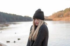 Muchacha blanda en un suéter y un sombrero calientes que presentan afuera en día de invierno soleado Foto de archivo