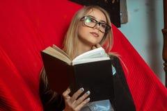 Muchacha blanda en vidrios con un libro negro en sus manos en una silla Foto de archivo