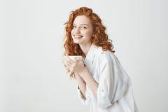 Muchacha blanda feliz del pelirrojo en camisa que sonríe sosteniendo la taza que mira la cámara que se sienta en la tabla Fondo b Imagen de archivo