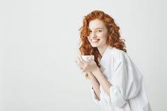 Muchacha blanda feliz del pelirrojo en camisa que sonríe sosteniendo la taza que mira la cámara que se sienta en la tabla Fondo b Imagen de archivo libre de regalías
