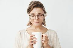 Muchacha blanda hermosa en los vidrios que sostienen la taza que mira abajo sobre el fondo blanco Foto de archivo libre de regalías