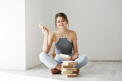Muchacha blanda hermosa joven que sonríe mirando la cámara que sostiene el libro que se sienta en piso sobre la pared blanca temp Imagen de archivo
