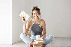 Muchacha blanda hermosa joven que sonríe mirando la cámara que sostiene el libro que se sienta en piso sobre la pared blanca temp Imagen de archivo libre de regalías