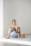 Muchacha blanda hermosa joven que sonríe sosteniendo el libro que se sienta en piso sobre la pared blanca temprano por mañana Fotos de archivo