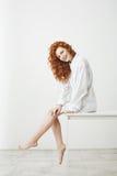 Muchacha blanda hermosa linda con el pelo rojo rizado que ríe planteando sentarse en la tabla sobre el fondo blanco Copie el espa Fotografía de archivo libre de regalías