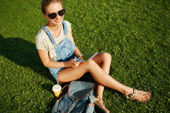 Muchacha blondy joven que usa la sentada al aire libre de la tableta en gras fotos de archivo libres de regalías