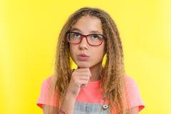 Muchacha bonita 12-13 años rubios con el pelo rizado con los vidrios, miradas pensativamente a un lado, pensando en escuela Expre Imagenes de archivo