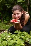 Muchacha bonita adolescente con el puñado de fresas maduras Foto de archivo libre de regalías