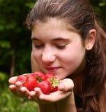 Muchacha bonita adolescente con el puñado de fresas maduras Fotos de archivo libres de regalías
