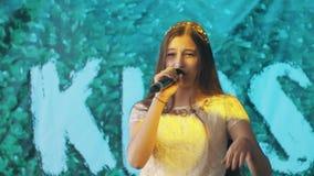 Muchacha bonita adolescente en vestido que canta en microfone en la demostración almacen de metraje de vídeo