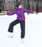 Muchacha bonita adolescente que patina en la pista de hielo Imagenes de archivo