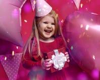 Muchacha bonita adorable con los globos rosados y regalo del rojo el actuales y casquillo del cumpleaños Fotos de archivo