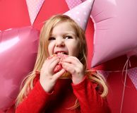 Muchacha bonita adorable con los globos rosados y regalo del rojo el actuales y casquillo del cumpleaños Foto de archivo libre de regalías