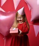 Muchacha bonita adorable con los globos rosados y regalo del rojo el actuales y casquillo del cumpleaños Foto de archivo