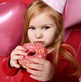 Muchacha bonita adorable con los globos rosados y regalo del rojo el actuales y casquillo del cumpleaños Imagen de archivo libre de regalías