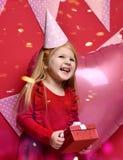 Muchacha bonita adorable con los globos rosados y regalo del rojo el actuales y casquillo del cumpleaños Fotos de archivo libres de regalías