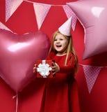 Muchacha bonita adorable con los globos rosados y regalo del rojo el actuales y casquillo del cumpleaños Imagenes de archivo