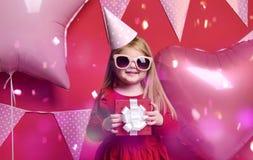 Muchacha bonita adorable con los globos rosados y regalo del rojo el actuales y casquillo del cumpleaños Fotografía de archivo