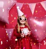 Muchacha bonita adorable con los globos rosados y regalo del rojo el actuales y casquillo del cumpleaños Imagen de archivo