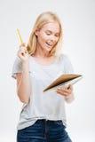 Muchacha bonita alegre de risa que sostiene el cuaderno Fotos de archivo libres de regalías