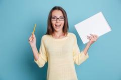 Muchacha bonita alegre de risa que sostiene el cuaderno sobre fondo azul Imagen de archivo libre de regalías
