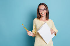 Muchacha bonita alegre de risa que sostiene el cuaderno sobre fondo azul Imagenes de archivo